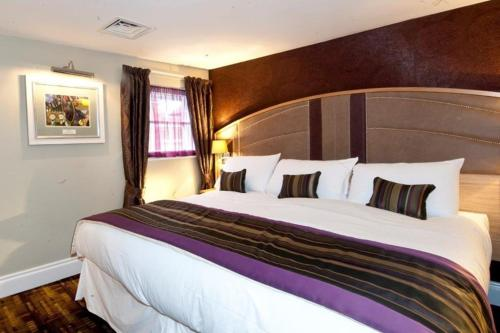A bed or beds in a room at The Golden Lion Wetherspoon