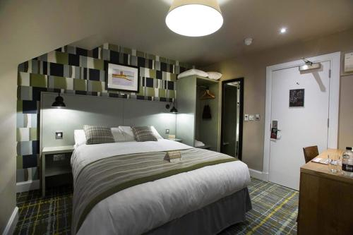 A bed or beds in a room at Jolly's Hotel Wetherspoon