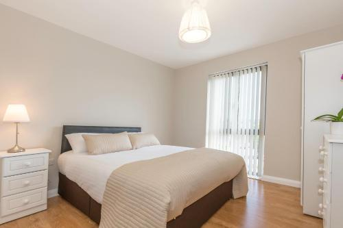 A bed or beds in a room at Bt1 Apartments - Ivy House