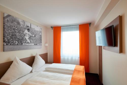 A bed or beds in a room at McDreams Hotel Mönchengladbach