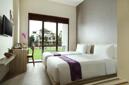 A bed or beds in a room at The Evitel Resort Ubud