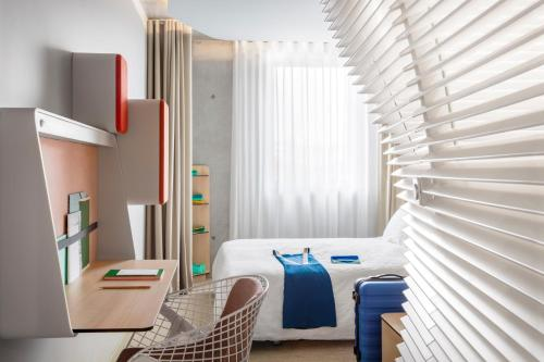 A bed or beds in a room at Okko Hotels Cannes Centre