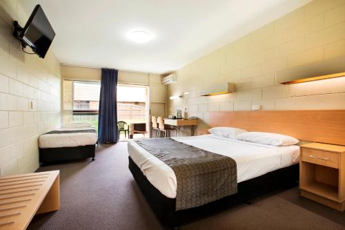A bed or beds in a room at Dalrymple Hotel