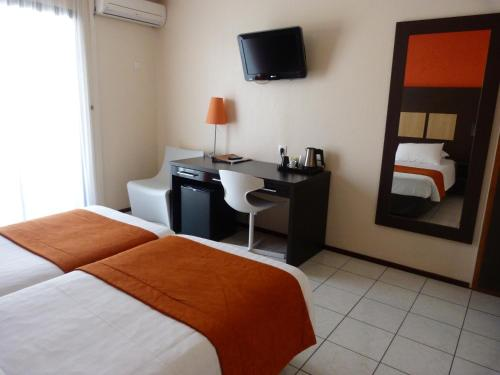 A bed or beds in a room at Central Hotel Cayenne
