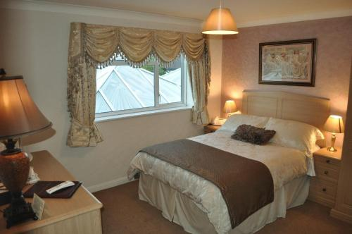 A bed or beds in a room at Ardmore House Hotel