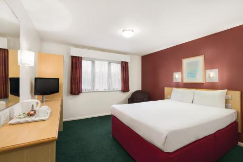 A bed or beds in a room at Days Inn London Stansted Airport