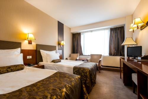 A bed or beds in a room at Grand Hotel Napoca