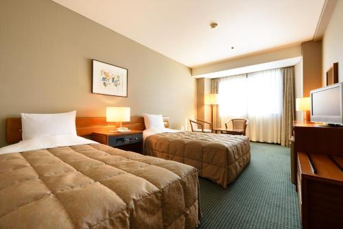 A bed or beds in a room at Hotel Royal Morioka