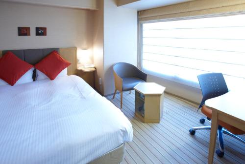 A bed or beds in a room at Pearl Hotel Yaesu