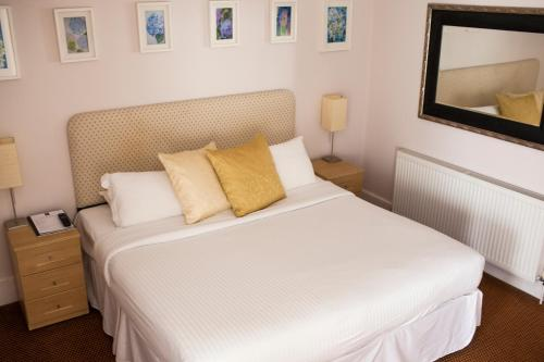 A bed or beds in a room at OYO White Horse Hotel