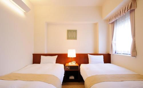 A bed or beds in a room at Chisun Hotel Kobe