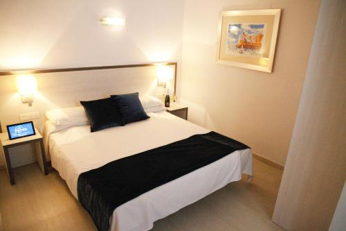 A bed or beds in a room at Parrots Sitges Hotel