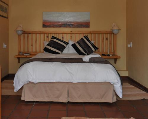 A bed or beds in a room at De Werf Lodge