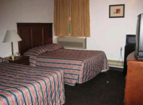 A bed or beds in a room at Martin House Motel Brookfield