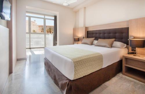 A bed or beds in a room at Catalonia Mirador des Port