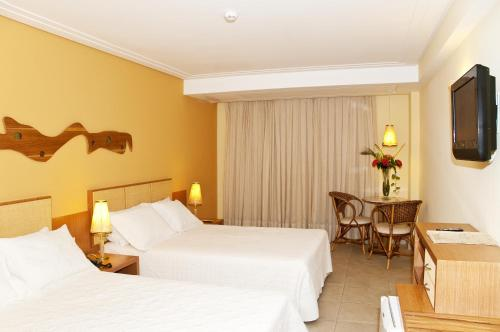 A bed or beds in a room at Pontalmar Praia Hotel