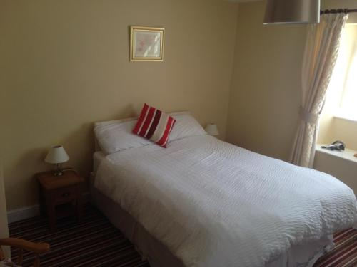 A bed or beds in a room at The Tally Ho Inn