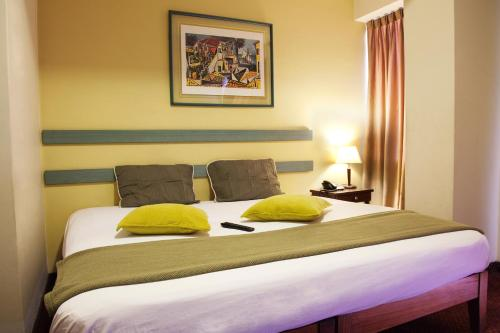 A bed or beds in a room at Kamana Hotel