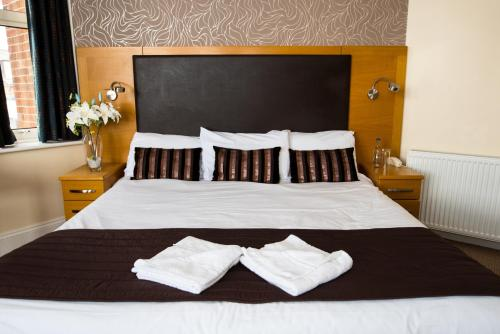 A bed or beds in a room at Palm Court Hotel