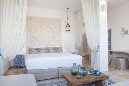 A bed or beds in a room at Falkensteiner Resort Capo Boi
