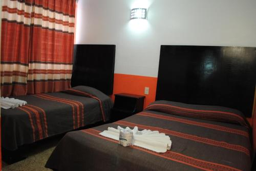 A bed or beds in a room at Hotel Jiménez