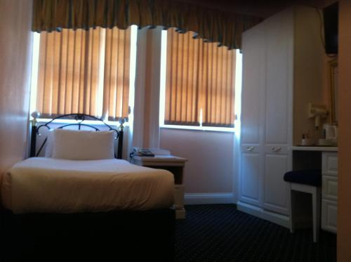 A bed or beds in a room at Mermaid Suite Hotel