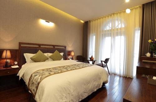 A bed or beds in a room at Sapa Legend Hotel & Spa