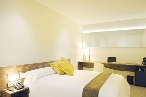 A bed or beds in a room at Air Rooms Madrid Airport By Premium Traveller