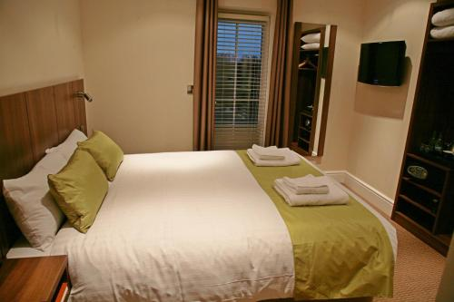 A bed or beds in a room at The Buxted Inn