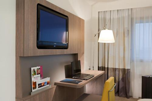 A television and/or entertainment center at Novotel Brussels City Centre
