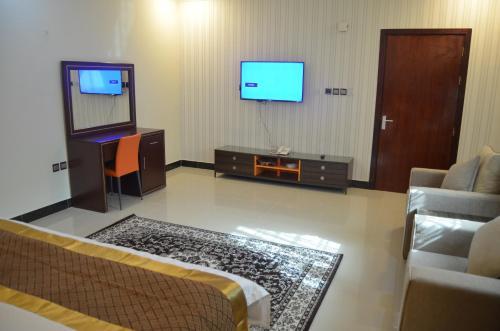 Uma TV ou centro de entretenimento em Almanzel Althahabi Aparthotel