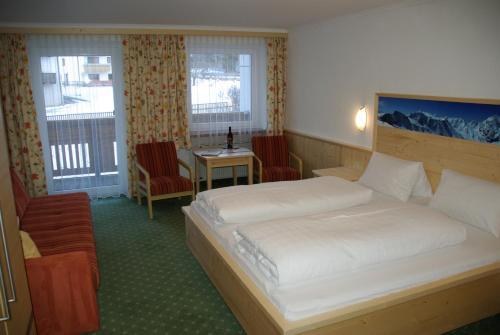 A bed or beds in a room at Alpenhof Pension-Garni