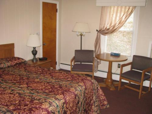A bed or beds in a room at The Colonial Inn & Motel