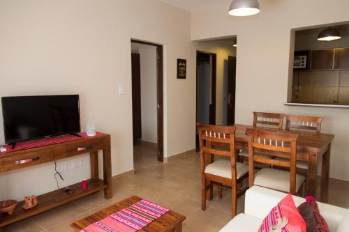 Una televisión o centro de entretenimiento en Las Tulmas Apart Hotel