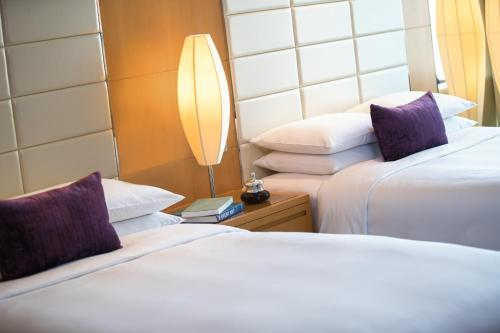 A bed or beds in a room at Renaissance Shanghai Putuo Hotel
