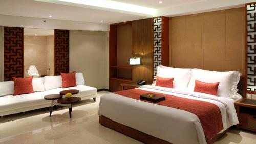 A bed or beds in a room at The Bandha Hotel & Suites