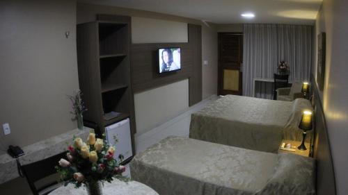 A bed or beds in a room at Amuarama Hotel