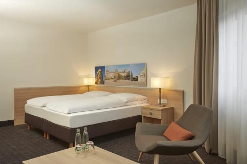 A bed or beds in a room at H+ Hotel Darmstadt