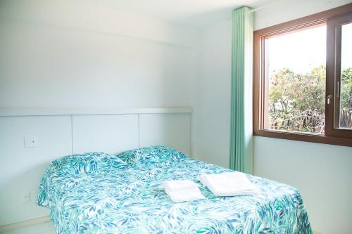 A bed or beds in a room at Apt. Enseada Praia do Forte