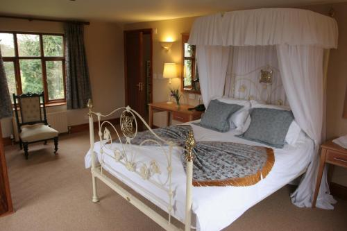 A bed or beds in a room at Ivy House Country Hotel