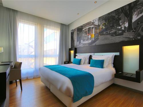 A bed or beds in a room at Jupiter Lisboa Hotel
