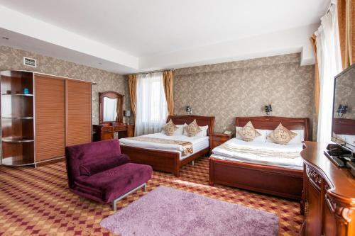 A bed or beds in a room at UB City Hotel