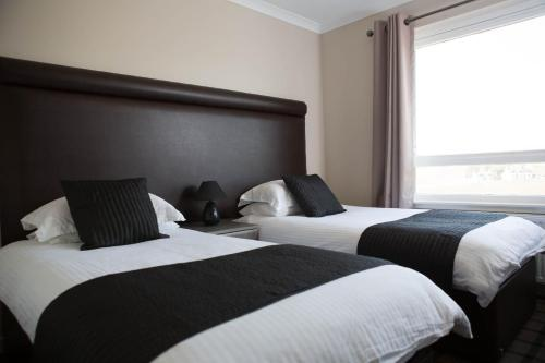 A bed or beds in a room at The Greenside Hotel