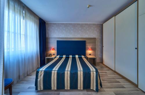 A bed or beds in a room at Hotel Alberi