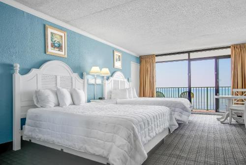 A bed or beds in a room at Sand Dunes Resort & Suites