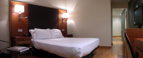 A bed or beds in a room at AC Hotel Almería by Marriott