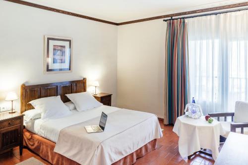 A bed or beds in a room at Parador de Manzanares