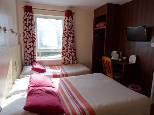 A bed or beds in a room at The Gatwick White House Hotel