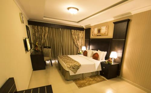 A bed or beds in a room at Ivory Grand Hotel Apartments