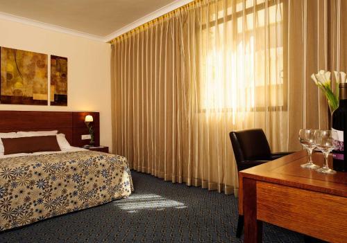 A bed or beds in a room at Caesar Premier Jerusalem Hotel